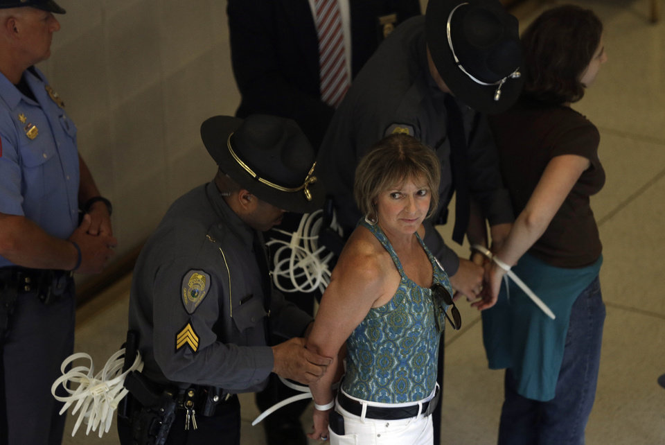 Photo - Protestors are arrested outside the Senate chamber at the state legislature in Raleigh, N.C., Monday, June 17, 2013.  The National Association for the Advancement of Colored People and supporters of what the group calls