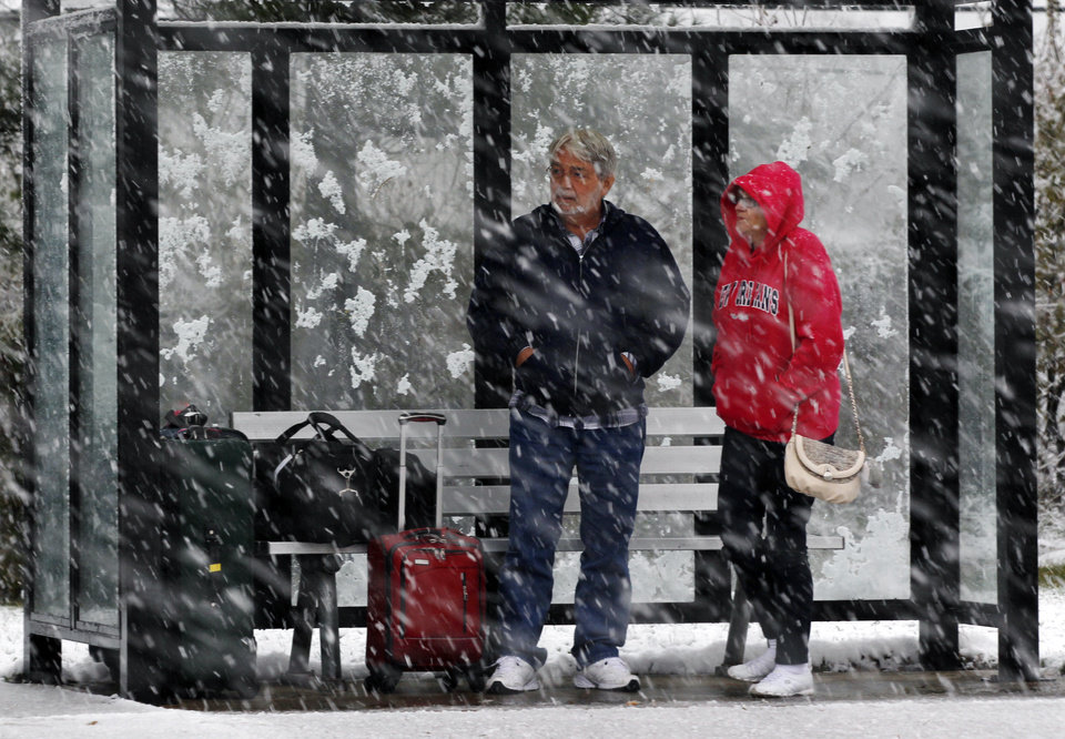 Photo - A couple stands in a bus shelter during a snowfall Wednesday, Nov. 7, 2012, in Dover Township, N.J., as the region pounded by Superstorm Sandy last week is hit by a Nor'Easter.  Gov. Chris Christie warned Wednesday that New Jersey may suffer a setback in its Superstorm Sandy recovery efforts as a result of the new storm. (AP Photo/Mel Evans) ORG XMIT: NJME111