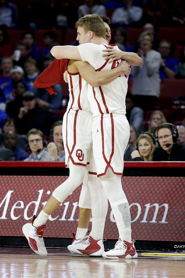Photo - Oklahoma's Jamuni McNeace (4) hugs Hannes Polla (44) as he enters the game during the men's college basketball game between the University of Oklahoma and Kansas at the Lloyd Noble Center in Norman, Okla., Tuesday, March 5, 2019. Photo by Sarah Phipps, The Oklahoman