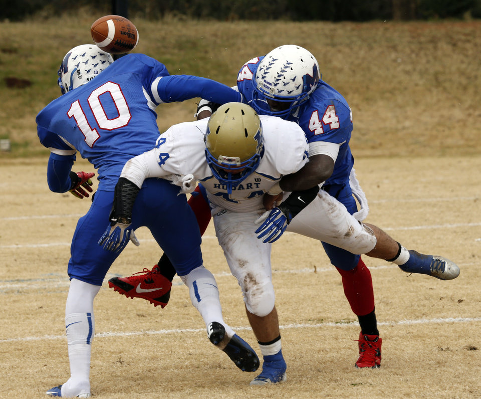 Photo - Hobart's Aaron Hernandez fumbles the ball out of bounds on the hit from Alfonzo McMillian (10 and Larry Lambeth (44) as Millwood plays Hobart in high school football playoff action on Saturday, Nov. 23, 2013, in Oklahoma City, Okla. Photo by Steve Sisney, The Oklahoman