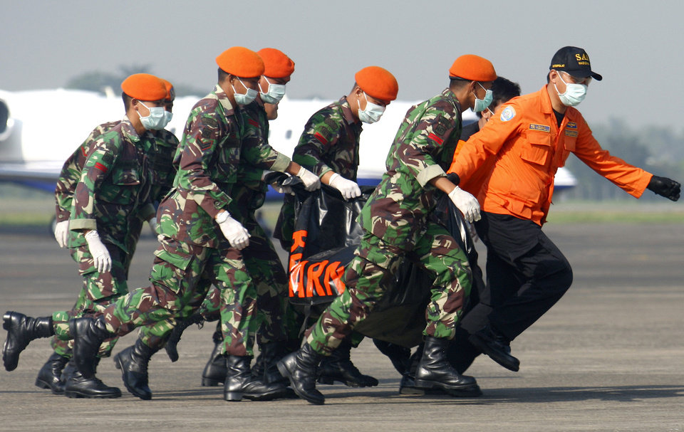 Photo -   Rescuers carry a body bag containing the body of a victim of a Russian-made jetliner's crash upon arrival at Halim Perdanakusumah airport in Jakarta, Indonesia, Saturday, May 12, 2012. Search teams who scaled a volcano's steep slopes found at least 12 bodies Friday near the wreckage of the Sukhoi Superjet-100 that crashed in Indonesia during a demonstration flight for potential buyers, an official said. (AP Photo/Tatan Syuflana)