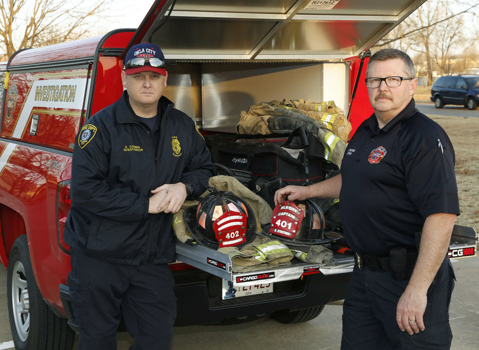 Photo -  Oklahoma City fire investigators Steve Strother and Brian Cosner stand beside their fire investigation truck at the Oklahoma City Fire Prevention Office. [Photo by Paul Hellstern, The Oklahoman]