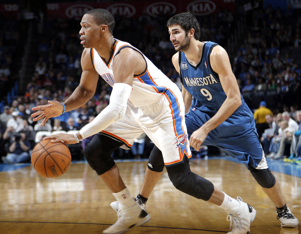 Photo - Oklahoma City's Russell Westbrook (0) drives past Minnesota's Ricky Rubio (9) during the NBA game between the Oklahoma City Thunder and the Minnesota Timberwolves at the Chesapeake Energy Arena, Sunday, Dec. 1, 2013. Photo by Sarah Phipps, The Oklahoman