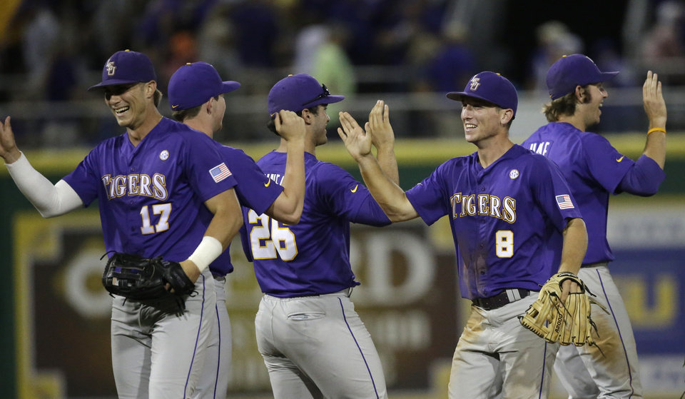 Photo - LSU outfielder Jared Foster (17), catcher Chris Chinea (26) and infielder Alex Bregman (8) celebrate their 5-1 victory over Houston after an NCAA college baseball regional tournament game in Baton Rouge, La., Saturday, May 31, 2014. (AP Photo/Gerald Herbert)