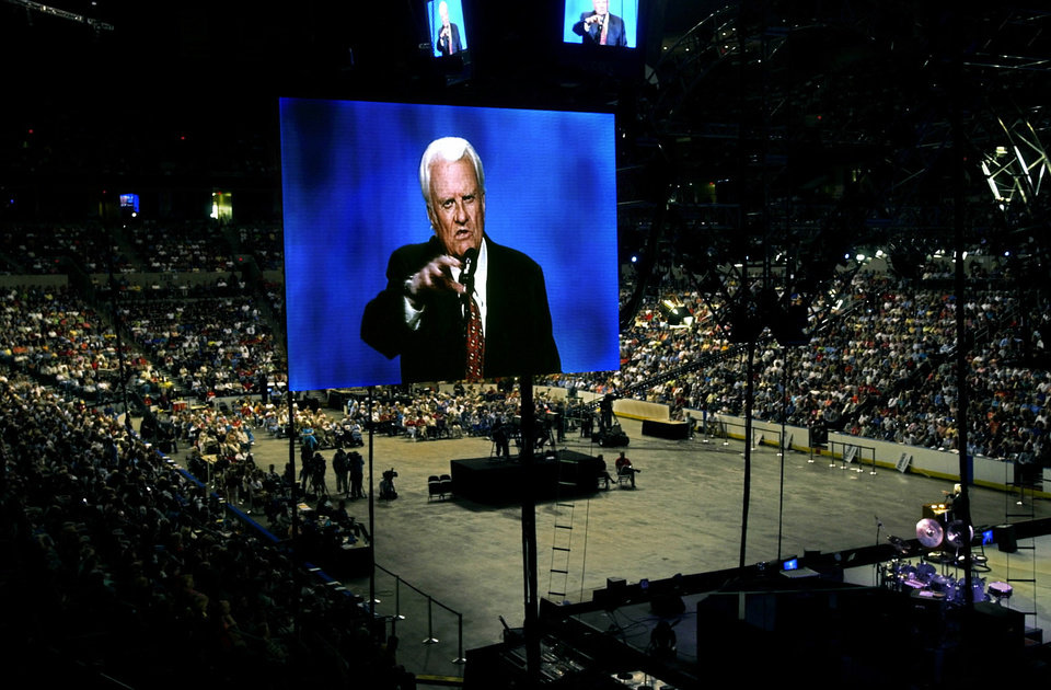 Photo - Oklahoma City, Thursday, June 12, 2003.  Billy Graham is seen on a large screen tv over the crowd at the Ford Center during the Mission Oklahoma City featuring Billy Graham.  Staff photo by Bryan Terry