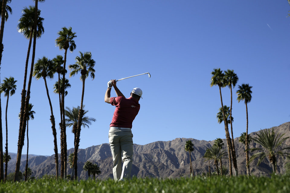 Photo - Robert Garrigus watches his tee shot on the 18th hole during the first round of the Humana Challenge golf tournament at the La Quinta Country Club on Thursday, Jan. 16, 2014 in La Quinta, Calif. (AP Photo/Chris Carlson)