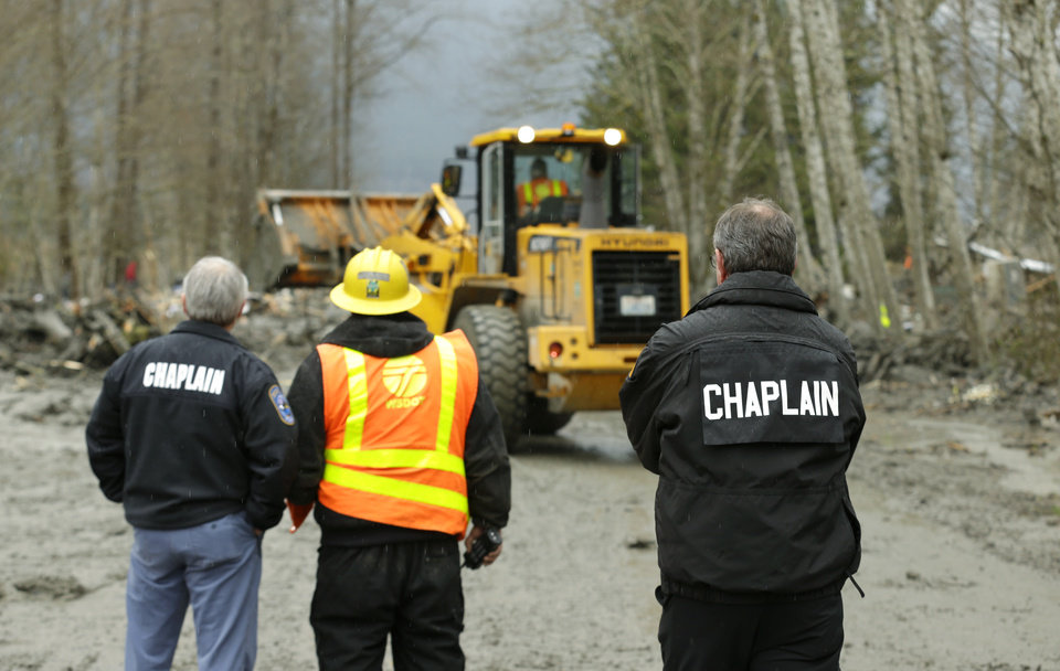 Photo - Washington State Patrol chaplains Joel Smith, left, and Mike Neil, right, watch as workers using heavy equipment work to clear debris, Tuesday, March 25, 2014, from Washington Highway 530 on the western edge of the massive mudslide that struck near Arlington, Wash. Saturday, killing at least 14 people and leaving dozens missing. (AP Photo/Ted S. Warren, Pool)