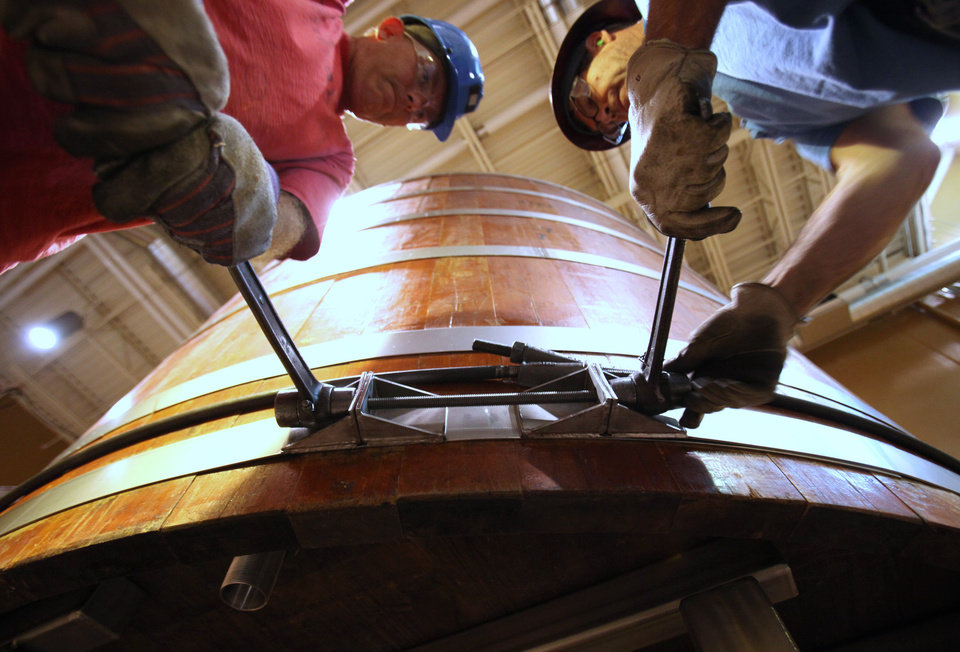 Photo - FILE - In this Aug. 15, 2013, file photo, Bill Wehr, left, of Arrow Tank company in Buffalo, N.Y., and custom builder and woodworker Rock Bartley of Kalamazoo, Mich., tighten the bands while assembling the 100-year-old wooden barrels from Stroh's, in Constock, Mich. Bell's Brewery said it plans to open a new pub the week of Monday, Sept. 16, 2013, at Gerald Ford International Airport in Grand Rapids. It will be similar to but smaller than Bell's Eccentric Cafe in Kalamazoo. (AP Photo/Kalamazoo Gazette/mlive.com , Mark Bugnaski, File)