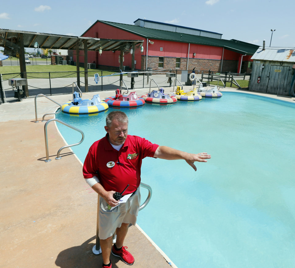 Photo -  Cliff Bristow, director of operations at Andy Alligator's Fun Park, shows the bumper boat area that will be replaced with added recreational space when the building in the background gets an 8,000-square-foot expansion. PHOTO BY STEVE SISNEY, THE OKLAHOMAN   STEVE SISNEY -