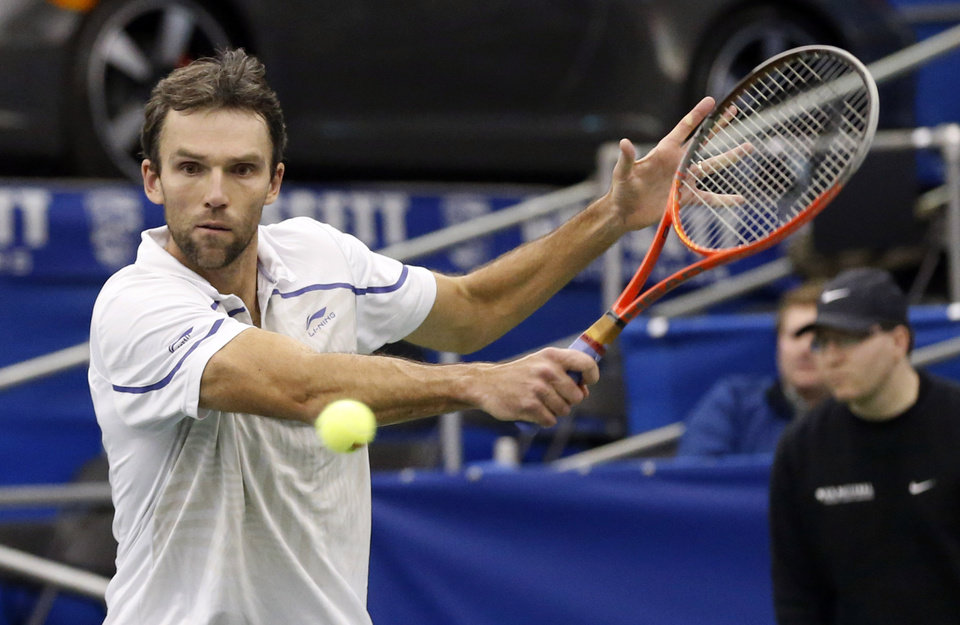 Photo - Ivo Karlovic, of Croatia, hits a return to Feliciano Lopez, of Spain, during the U.S. National Indoor Tennis Championships on Thursday, Feb. 13, 2014, in Memphis, Tenn. (AP Photo/Rogelio V. Solis)