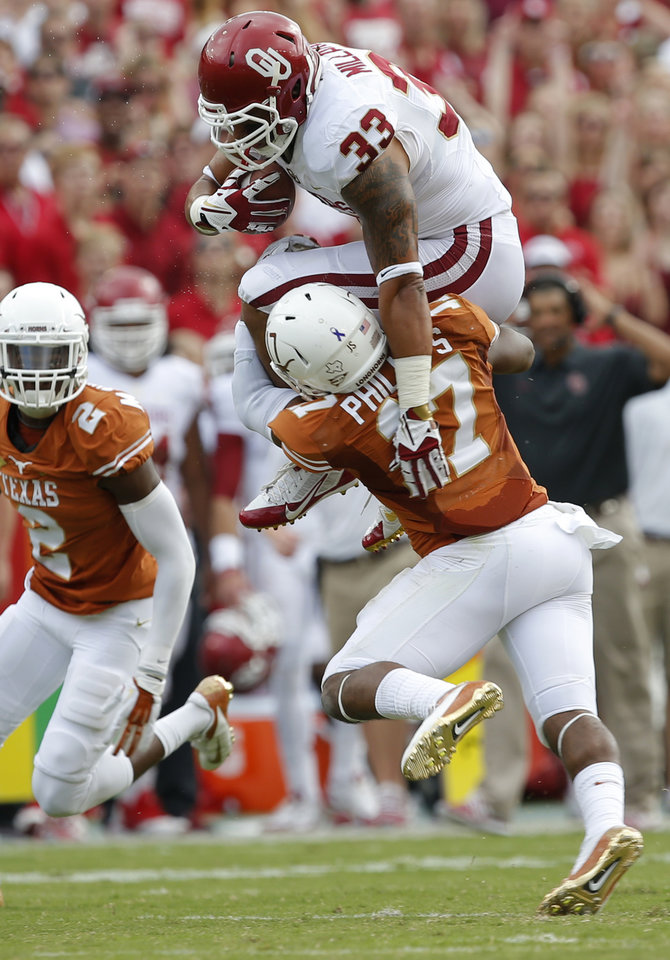 Photo - OU's Trey Millard (33) tries to leap past UT's Adrian Phillips (17) and Mykkele Thompson (2) during the Red River Rivalry college football game between the University of Oklahoma Sooners and the University of Texas Longhorns at the Cotton Bowl Stadium in Dallas, Saturday, Oct. 12, 2013. Photo by Bryan Terry, The Oklahoman