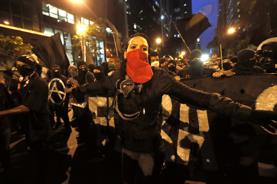Photo - Masked members of the so-called Black Bloc anarchist group join in a march in support of striking teachers, marking National Teachers Day, in Rio de Janeiro, Brazil, Tuesday, Oct. 15, 2013. Teachers have been on strike demanding better pay for more than two months. Last week, a largely peaceful rally turned violent in Rio when small groups of masked protesters started hurling rocks and gasoline bombs at banks, stores and restaurants and set fire to a passenger bus. During the march Black Bloc anarchists tried to incite the crowd, but were kept in check by other demonstrators. (AP Photo/Silvia Izquierdo)