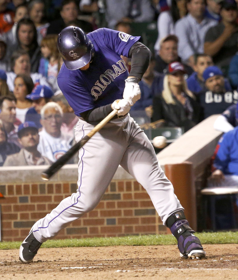 Photo - Colorado Rockies' Nolan Arenado hits an RBI single off Chicago Cubs starting pitcher Tsuyoshi Wada, scoring Charlie Blackmon, during the sixth inning of a baseball game Monday, July 28, 2014, in Chicago. (AP Photo/Charles Rex Arbogast)