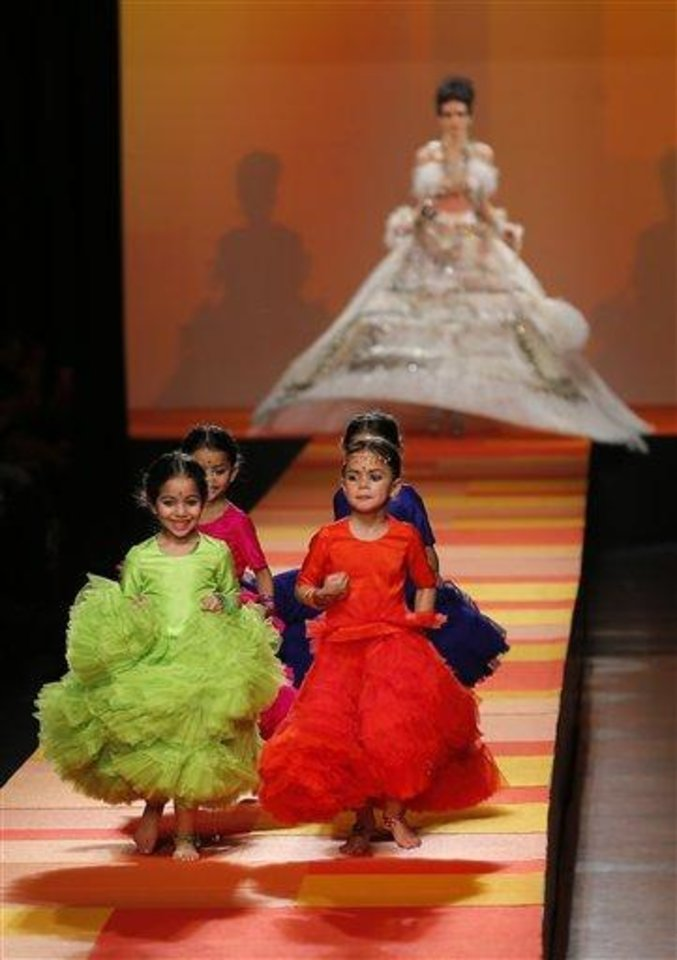 Children run ahead of a model wearing the weeding gown for French fashion fashion designer Jean-Paul Gaultier's Spring-Summer 2013 Haute Couture fashion collection, presented in Paris, Wednesday, Jan.23, 2013. (AP Photo/Jacques Brinon)