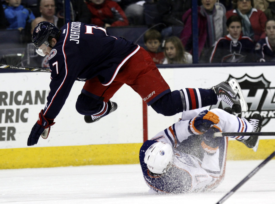 Columbus Blue Jackets' Jack Johnson, top, collides with Edmonton Oilers' Anton Belov, of Russia, in the second period of an NHL hockey game in Columbus, Ohio, Friday, Nov. 29, 2013. (AP Photo/Paul Vernon)