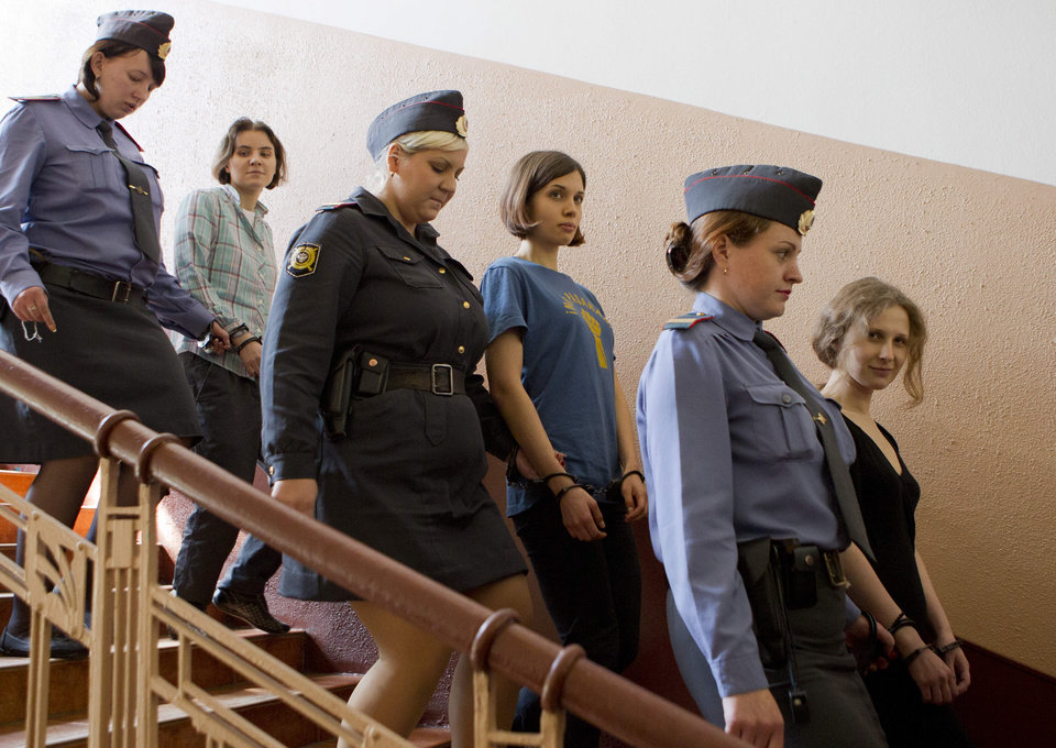Photo -   Feminist Russian punk group Pussy Riot members, Nadezhda Tolokonnikova, center, Maria Alekhina, right, and Yekaterina Samutsevich, are escorted to a glass cage at a court room in Moscow, Russia, Friday, Aug. 17, 2012. The three women in the band have been in jail for more than five months because of a prank they carried out in Moscow's main cathedral in a demonstration against Russia's Vladimir Putin, and they now face a maximum seven years in jail. (AP Photo/Misha Japaridze)