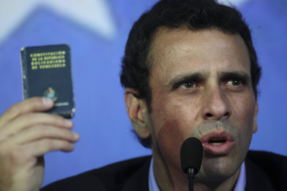 Opposition leader Henrique Capriles holds up a miniature copy of Venezuela's Constitution as he speaks during a press conference in Caracas, Venezuela, Friday, March 8, 2013. Capriles called Vice President Nicolas Maduro a bold-faced liar and accuses him of using Hugo Chavez's funeral to campaign for the presidency. (AP Photo/Rodrigo Abd)