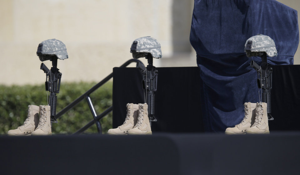Photo - A military memorial for fallen soldiers is displayed prior to a memorial ceremony for shooting victims that President Barack Obama will attend Wednesday, April 9, 2014, in Fort Hood, Texas. Last week's shooting rampage left four dead and more than a dozen injured. (AP Photo/Eric Gay)