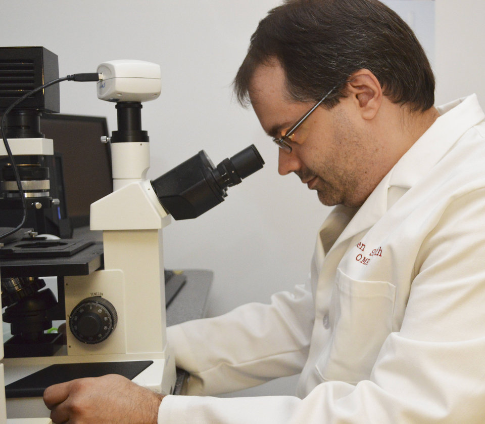 Photo - Oklahoma Medical Research Foundation scientist Dr. Ken Smith uses the microscope in the Human Antibody Core. Smith and his team are working on new research that could lead to better therapies for people with allergies. PHOTO PROVIDED.