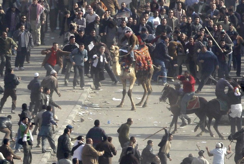 Photo -   FILE - In this Wednesday, Feb. 2, 2011 file photo, pro-government demonstrators, some riding camels and horses and armed with sticks, clash with anti-government demonstrators in Tahrir square, the center of anti-government demonstrations, in Cairo, Egypt. Egypt's state news agency said Wednesday, Oct. 10, 2012 that a Cairo court has acquitted 25 loyalists of ousted President Hosni Mubarak loyalists who had been accused of organizing an attack in which assailants on horses and camels charged into crowds of anti-regime protesters last year. (AP Photo/Ben Curtis, File)