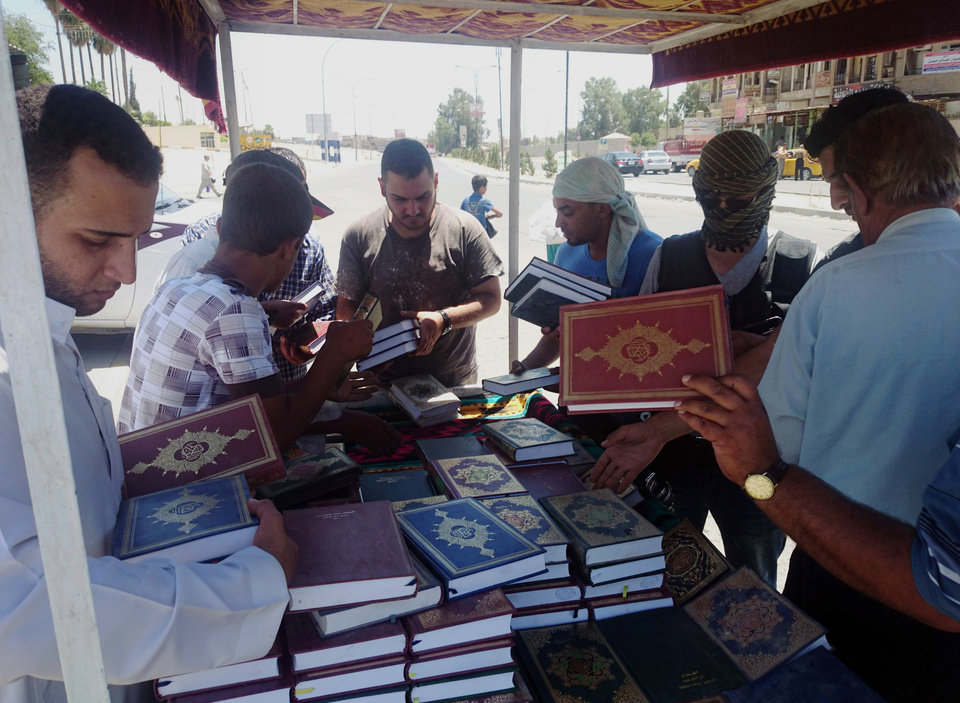 Photo - A fighter, third from right, with the al-Qaida-inspired Islamic State of Iraq and the Levant (ISIL) distributes copies of the Quran, Islam's holy book, to local residents in central northern city of Mosul, 225 miles (360 kilometers) northwest of Baghdad, Iraq, Sunday, June 22, 2014. Sunni militants on Sunday captured two border crossings, one along the frontier with Jordan and the other with Syria, security and military officials said, as they pressed on with their offensive in one of Iraq's most restive regions. (AP Photo)