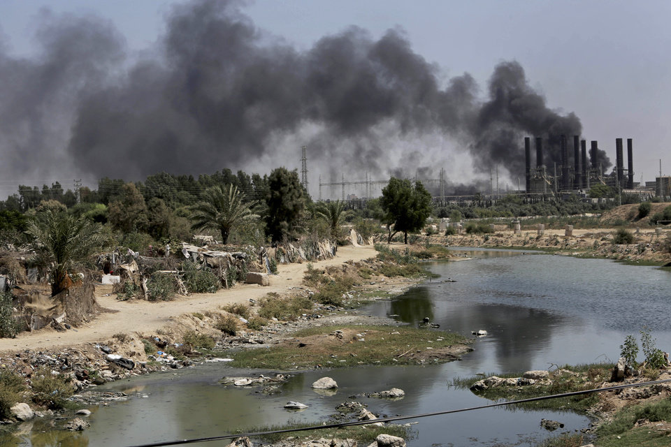 Photo - Smoke rises from the Gaza power plant after it was hit by Israeli strikes, in the Nusseirat refugee camp, central Gaza Strip,Tuesday, July 29, 2014. Israel escalated its military campaign against Hamas on Tuesday, striking symbols of the group's control in Gaza and firing tank shells that shut down the strip's only power plant in the heaviest bombardment in the fighting so far. The plant's shutdown was bound to lead to further serious disruptions of the flow of electricity and water to Gaza's 1.7 million people. (AP Photo/Adel Hana)
