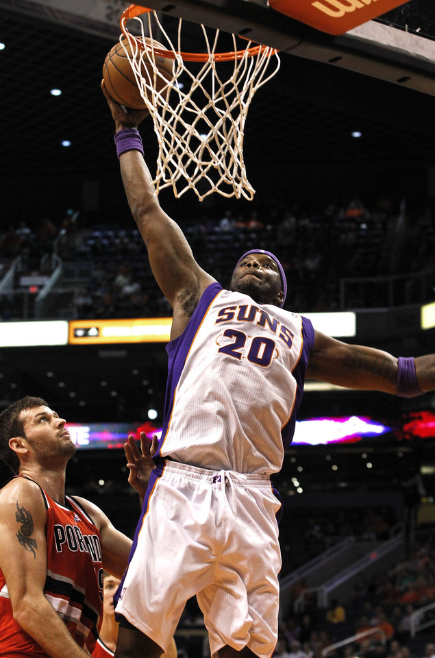 Photo -   Phoenix Suns' Jermaine O'Neal (20) goes in for a dunk as Portland Trail Blazers' Joel Freeland, of England, looks on during the second half of an NBA basketball game Wednesday, Nov. 21, 2012, in Phoenix. The Suns defeated the Trail Blazers 114-87. (AP Photo/Ross D. Franklin)