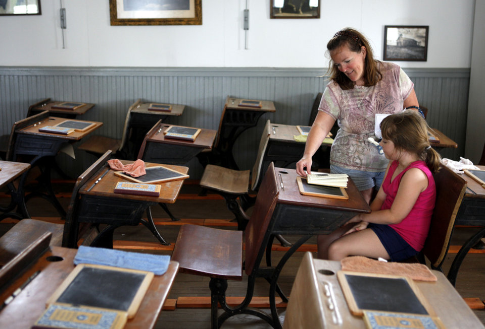 Photo - Kaylee Doughty and her mother, Pam Doughty, sit inside the Gant School House during last year's Living History Days at the Chisholm Trail Museum. Photo by Bryan Terry, The Oklahoman Archives  BRYAN TERRY - THE OKLAHOMAN