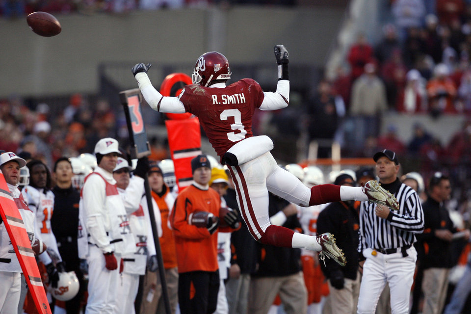 Photo - Reggie Smith tries to fly for an interception during the second half of the college football game between the University of Oklahoma Sooners (OU) and the Oklahoma State University Cowboys (OSU) at the Gaylord Family-Memorial Stadium on Saturday, Nov. 24, 2007, in Norman, Okla. 