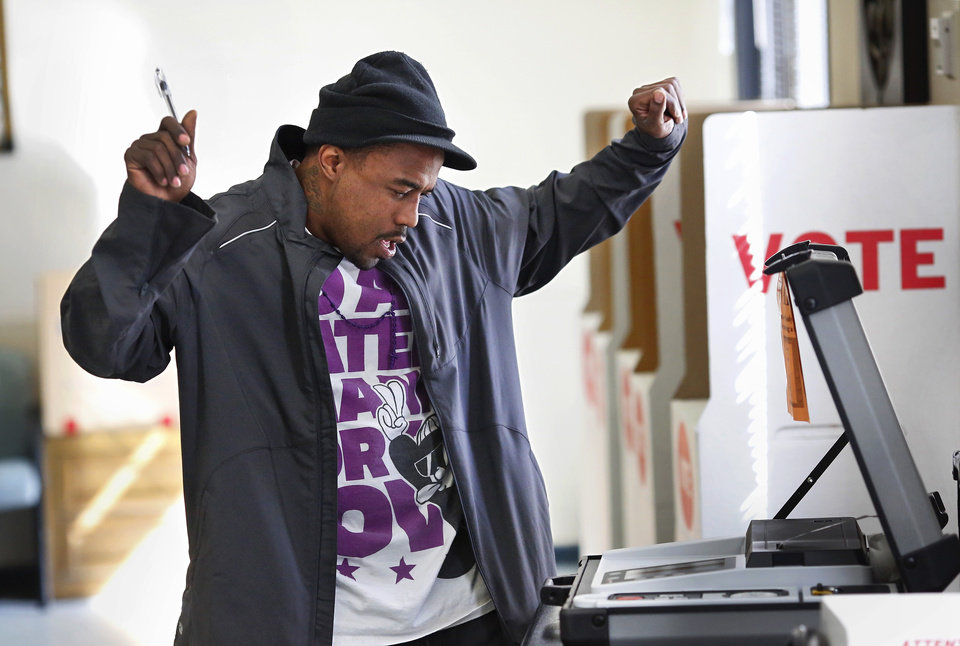 Photo - Voter Carey Foster raises his arms celebrate  his vote as the machine swallowed his ballot after voting in Precinct 240  in the Oklahoma City Council Ward 7 election on Tuesday, March 5, 2013. He voted at the McGuire Community Center on N. Lottie. Photo by Jim Beckel, The Oklahoman