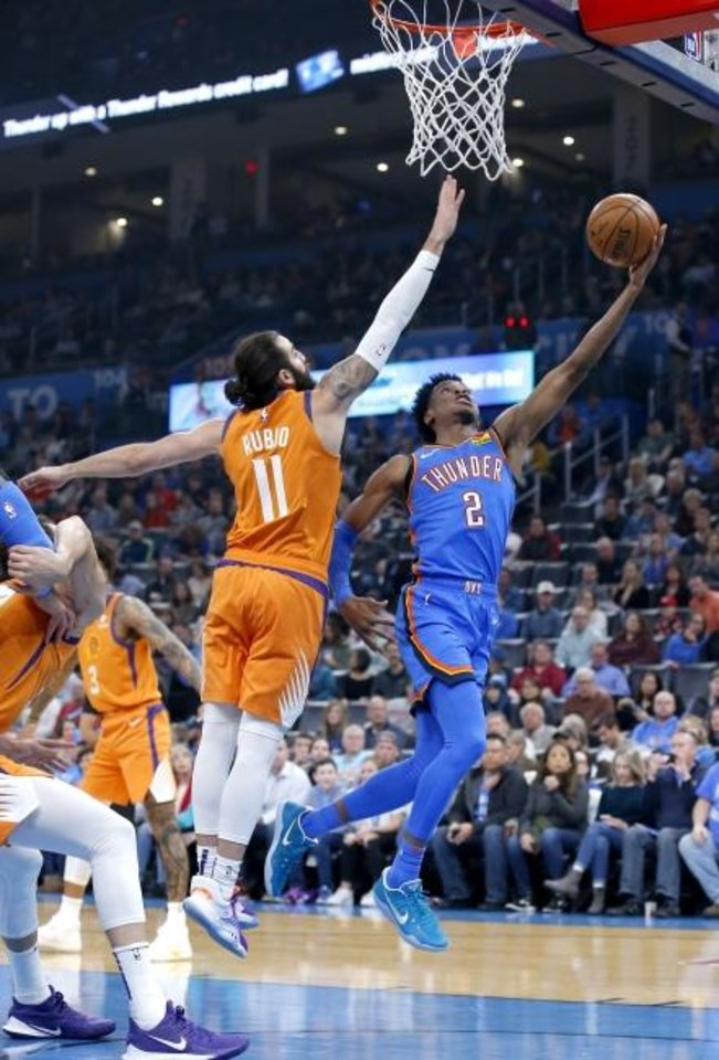 Photo -  Shai Gilgeous-Alexander, right, goes to the basket as Phoenix's Ricky Rubio defends during Friday night's game at Chesapeake Energy Arena. Oklahoma City won the game to reach .500 for the first time this season. [Sarah Phipps/The Oklahoman]