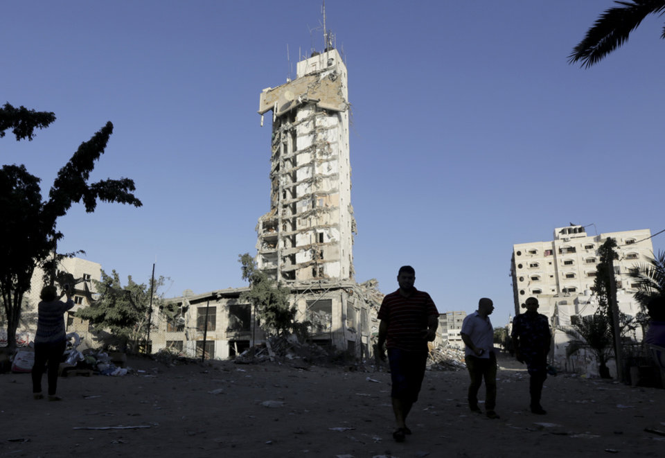 Photo - Palestinians walk in front of the damage to the Italian Complex following several late night Israeli airstrikes in Gaza City, in the northern Gaza Strip, Tuesday, Aug. 26, 2014. Israel bombed two Gaza City high-rises with dozens of homes and shops Tuesday, collapsing the 15-storey Basha Tower and severely damaging the Italian Complex in a further escalation in seven weeks of cross-border fighting with Hamas. (AP Photo/Adel Hana)