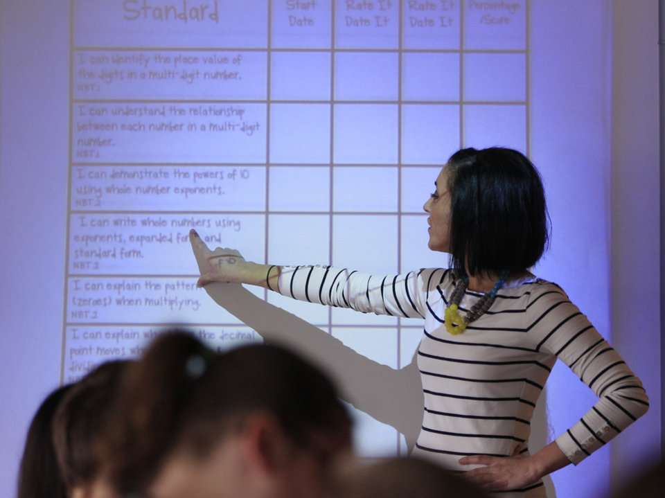 Photo -   In a photo from Sept. 14, 2012, Kristine Nannini points out information on a student data sheet she created to her fifth grade class at McGrath Elementary in Grand Blanc, Mich. Nannini spent her summer creating her own charts and student data sheets. It was something she imagined other teachers across the nation would want. So she decided to cash in on her prep time and sell her materials on teacherspayteachers.com. (AP Photo/Carlos Osorio)