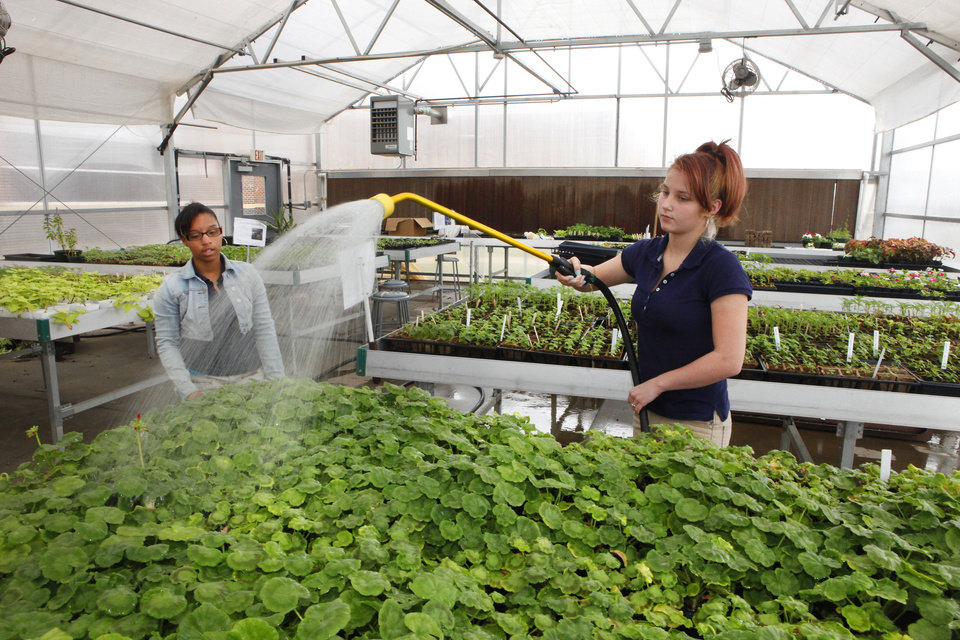 Photo - FFA student Kristina Hosea waters the plants with Jeanisha Bowen, left, in the John Marshall High School greenhouse. Photo By David McDaniel/The Oklahoman  David McDaniel - The Oklahoman