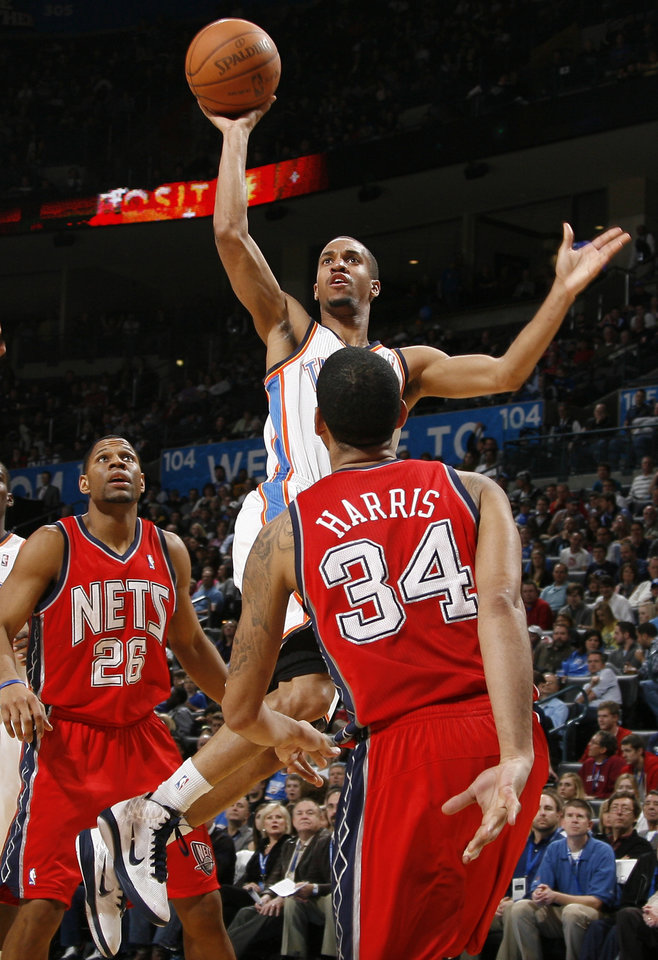 Photo - Oklahoma City's Eric Maynor shoots the ball from between New Jersey's Stephen Graham, left, and Devin Harris during the NBA basketball game between the Oklahoma City Thunder and the New Jersey Nets at the Oklahoma City Arena, Wednesday, Dec. 29, 2010.  Photo by Bryan Terry, The Oklahoman