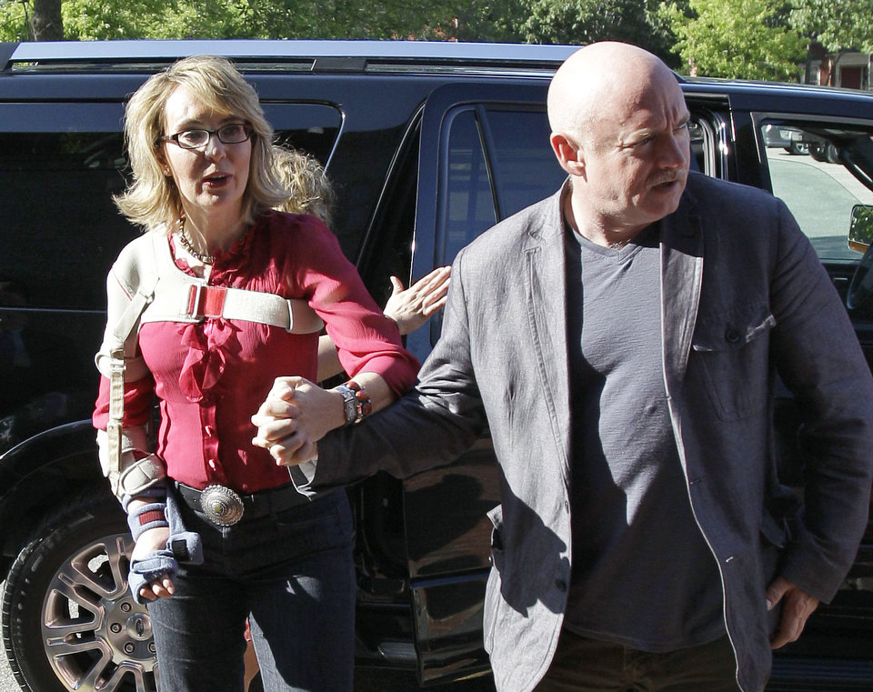 Photo - In this photo taken Friday, July 5, 2013, former Arizona Rep. Gabrielle Giffords and her husband, retired astronaut and combat veteran Capt. Mark Kelly, arrive to meet with local supporters and parents of Sandy Hook Elementary School victims at the Orchard Street Chop Shop in Dover, N.H.  Three years after being shot in the head, Giffords is in New Hampshire to urge support for background checks on gun purchases. (AP Photo/Mary Schwalm)