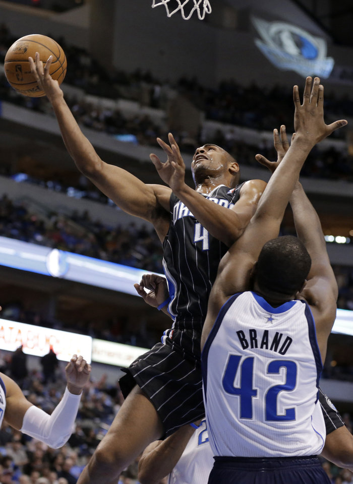 Orlando Magic's Arron Afflalo (4) loses control of the basket on a layup attempt as Dallas Mavericks' Elton Brand (42) defends in the first half of an NBA basketball game Wednesday, Feb. 20, 2013, in Dallas. (AP Photo/Tony Gutierrez)