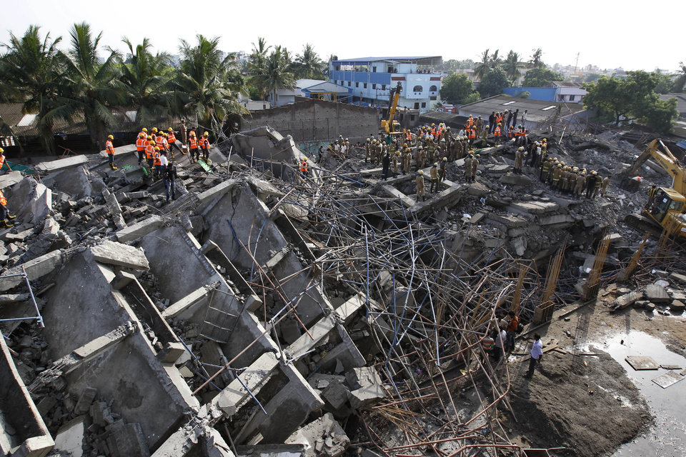 Photo - Rescuers search for workers believed buried in the rubble of a building that collapsed on the outskirts of Chennai, India, Sunday, June 29, 2014. The 12-story apartment structure the workers were building collapsed late Saturday while heavy rains and lightning were pounding. Police said 31 construction workers had been pulled out so far and the search was continuing for more than a dozen others. (AP Photo/Arun Sankar K)