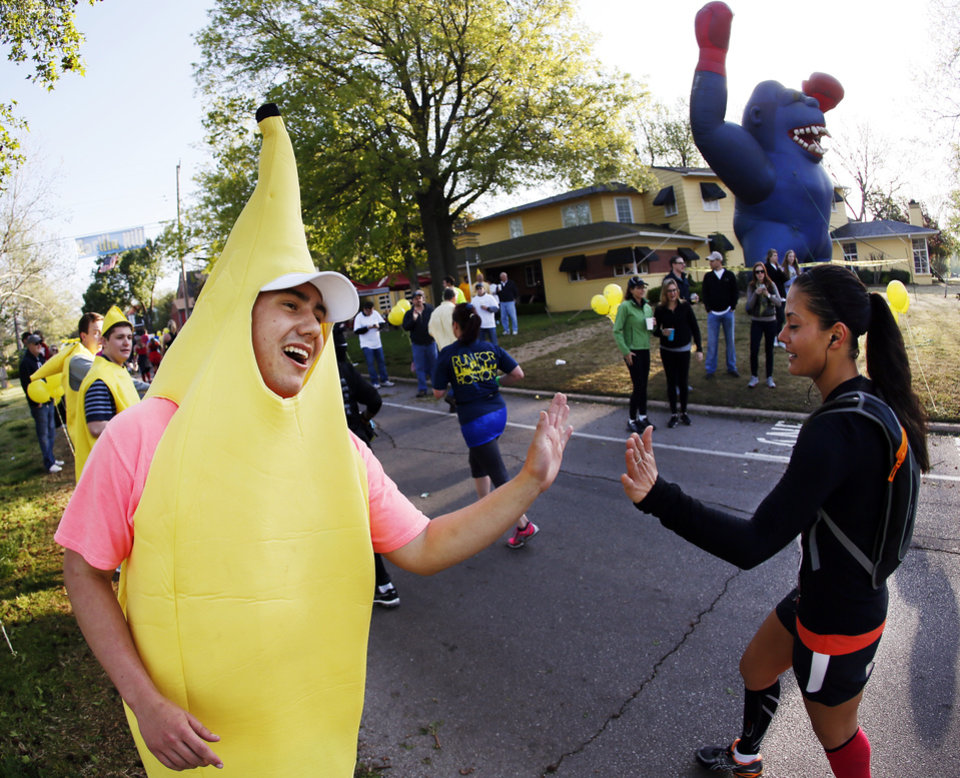 Photo - Mitch Halliman greets a runner making her way north on Shartel Ave. near NW 40th in the area known as Gorilla Hill during the Oklahoma City Memorial Marathon in Oklahoma City, Sunday, April 28, 2013. Photo by Nate Billings, The Oklahoman
