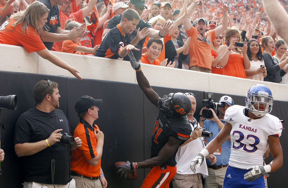 Oklahoma State's Justin Blackmon (81) celebrates a touchdown with fans in front of Kansas' Tyler Patmon (33) during the first half of the college football game between the Oklahoma State University Cowboys (OSU) and the University of Kansas Jayhawks (KU) at Boone Pickens Stadium in Stillwater, Okla., Saturday, Oct. 8, 2011. Photo by Sarah Phipp