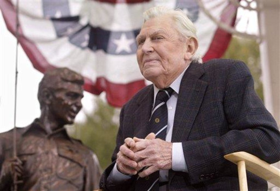 Photo - FILE - This Oct. 28, 2003 file photo shows actor Andy Griffith sitting in front of a bronze statue of Andy and Opie from the