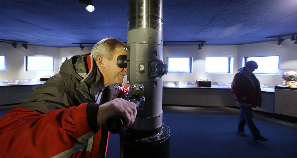 Photo - In this photo taken Wednesday, Dec. 26, 2012,  Gary Mill, of Boise, Idaho, peers through a periscope in the McCurdy Family Maritime Gallery at Seattle's Museum of History and Industry, in the city's South Lake Union neighborhood.