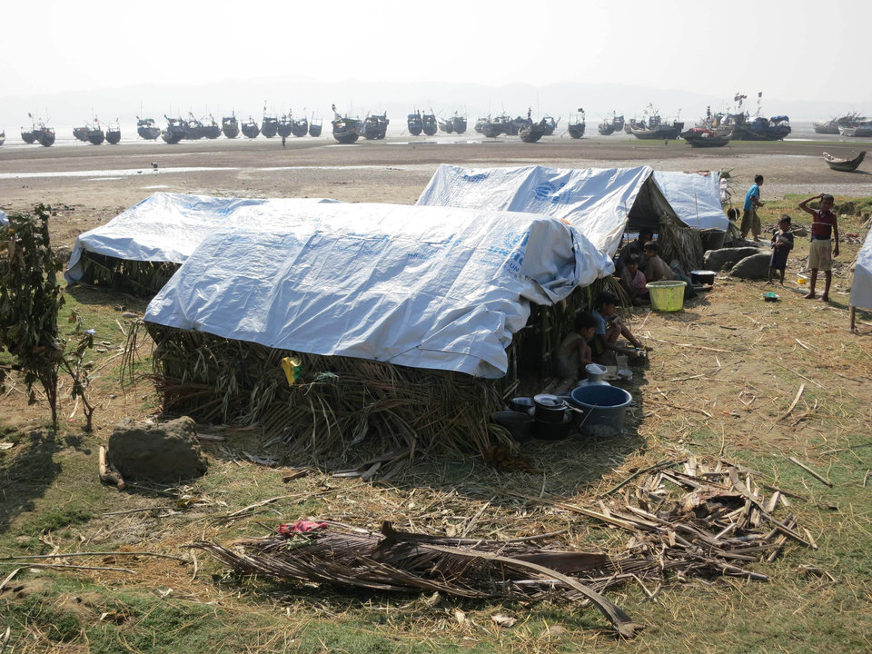 In this Nov. 11, 2012 photo, Muslim refugees who fled arson attacks that drove them from their neighborhood in the Myanmar port of Kyaukphu in late October sit under makeshift shelters beside their flotilla of wooden fishing boats on a beach in Sin Thet Maw, Myanmar. Stranded beside their decrepit flotilla of wooden boats, on a muddy beach far from home, the Muslim refugees tell story after terrifying story of their exodus from a once-peaceful town on Myanmar's western coast. The Oct. 24 exodus was part of a wave of violence that has shaken western Myanmar twice in the last six months. (AP Photo/Todd Pitman)