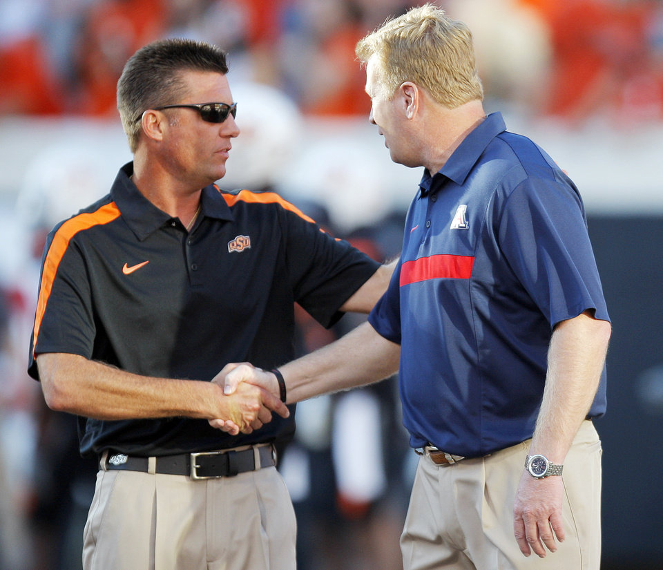 Photo - OSU head coach Mike Gundy, left, and Arizona head coach Mike Stoops shake hands before their game Thursday night. PHOTO BY NATE BILLINGS, The Oklahoman