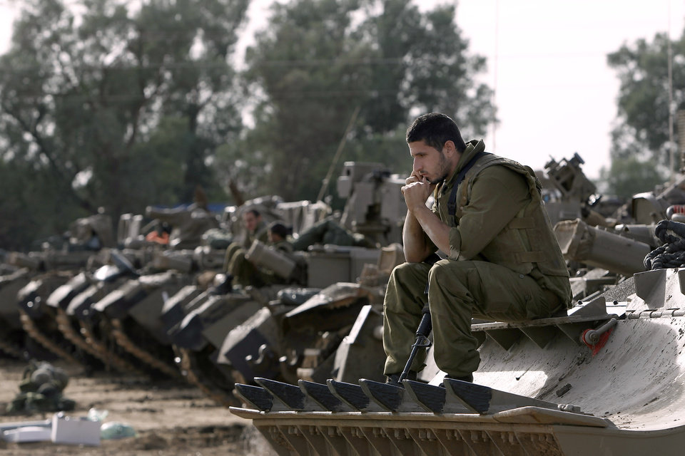 Israeli soldiers with armored vehicles gather in a staging ground near the border with Gaza Strip, southern Israel, Friday, Nov. 16, 2012. Fierce clashes between Israeli forces and Gaza militants are continuing for the third day.(AP Photo/Tsafrir Abayov) ORG XMIT: JRL149