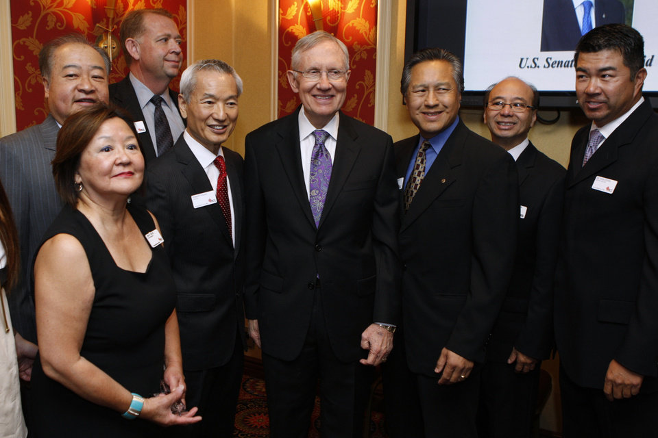 Photo - U.S. Sen. Harry Reid, D-Nev., center, takes photographs with members of the Asian Chamber of Commerce prior to taking the stage during their monthly lunch at the Gold Coast casino-hotel in Las Vegas. Reid, the Democratic Senate Majority Leader, apologized Friday for jokes he made about Asians during the luncheon. (AP Photo/Las Vegas Review-Journal, Erik Verduzco) LAS VEGAS SUN OUT