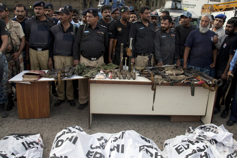 Photo - Pakistani police officers display confiscated ammunition and the dead bodies of terrorists who attacked the Jinnah International Airport Monday, June 9, 2014, in Karachi, Pakistan. Gunmen disguised as police guards attacked a terminal at Pakistan's busiest airport with machine guns and a rocket launcher during a five-hour siege that killed over a dozen people as explosions echoed into the night, while security forces retaliated and killed all the attackers, officials said Monday.  (AP Photo/Shakil Adil)