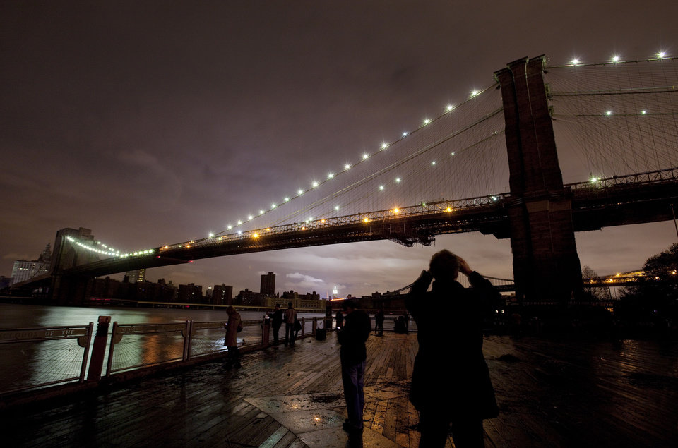 People photograph the Brooklyn Bridge and the Manhattan skyline, Tuesday, Oct. 30, 2012 in New York. Much of lower Manhattan is without electric power following the impact of superstorm Sandy. (AP Photo/Mark Lennihan) ORG XMIT: NYML124