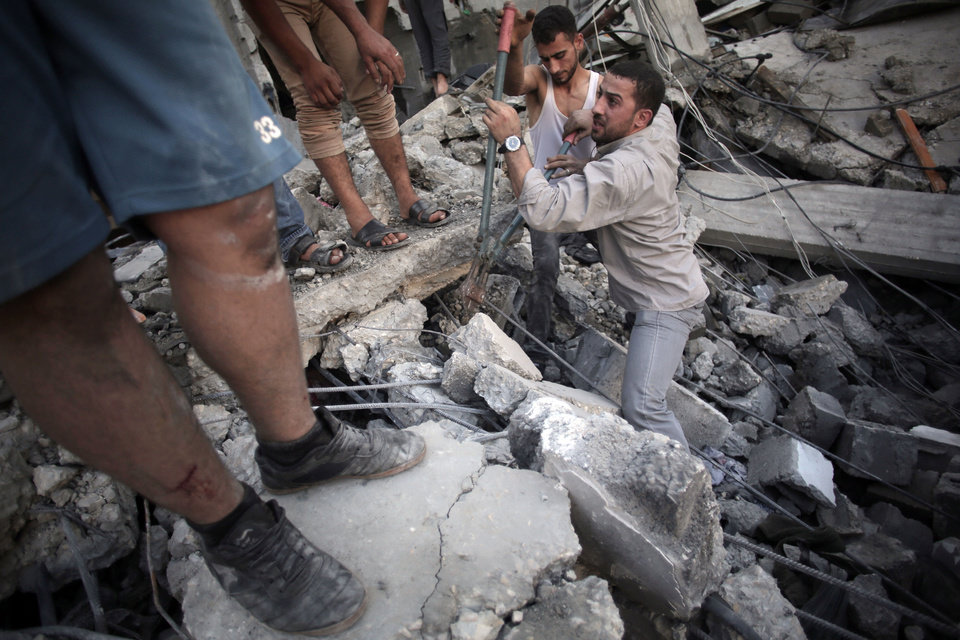 Photo - Palestinians search the rubble of a destroyed house where five members of the Ghannam family were killed in an Israeli missile strike early morning in Rafah refugee camp, southern Gaza Strip on Friday, July 11, 2014. Israel launched the Gaza offensive to stop incessant rocket fire that erupted after three Israeli teenagers were kidnapped and killed in the West Bank and a Palestinian teenager was abducted and burned to death in an apparent reprisal attack. The military says it has hit more than 1,100 targets already, mostly what it identified as rocket-launching sites, bombarding the territory on average every five minutes. (AP Photo/Khalil Hamra)