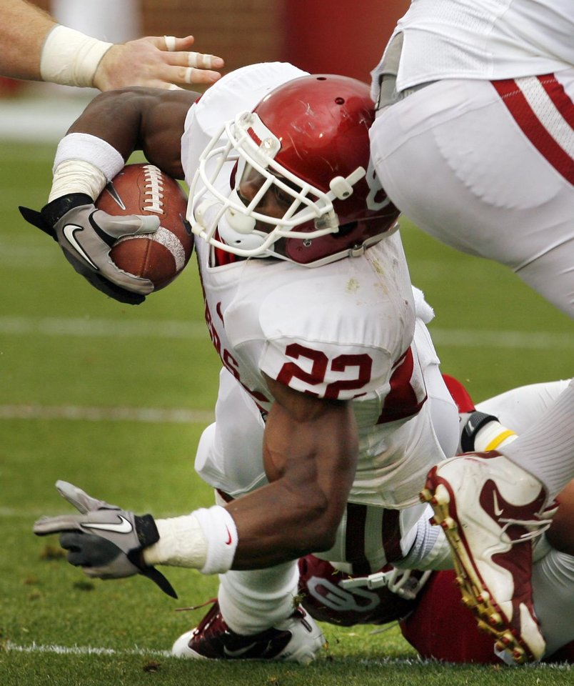 Roy Finch (22) stretches for extra yards with Londell Taylor (13) holding onto his ankles during the University of Oklahoma (OU) football team's annual Red and White Game at Gaylord Family/Oklahoma Memorial Stadium on Saturday, April 14, 2012, in Norman, Okla.  Photo by Steve Sisney, The Oklahoman